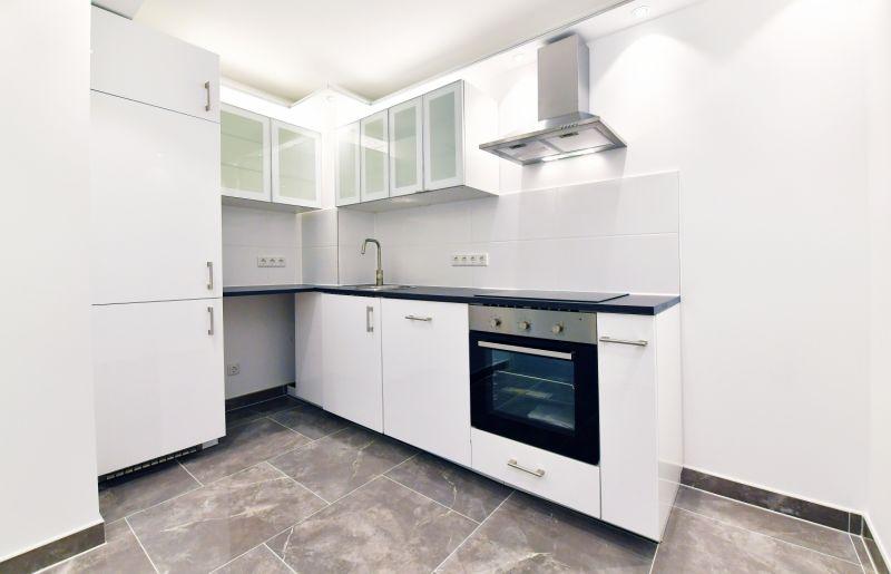 Voll ausgestattete Küche mit Geschirrspüler, beleuchteten Hängeschränken und Deckenspots
